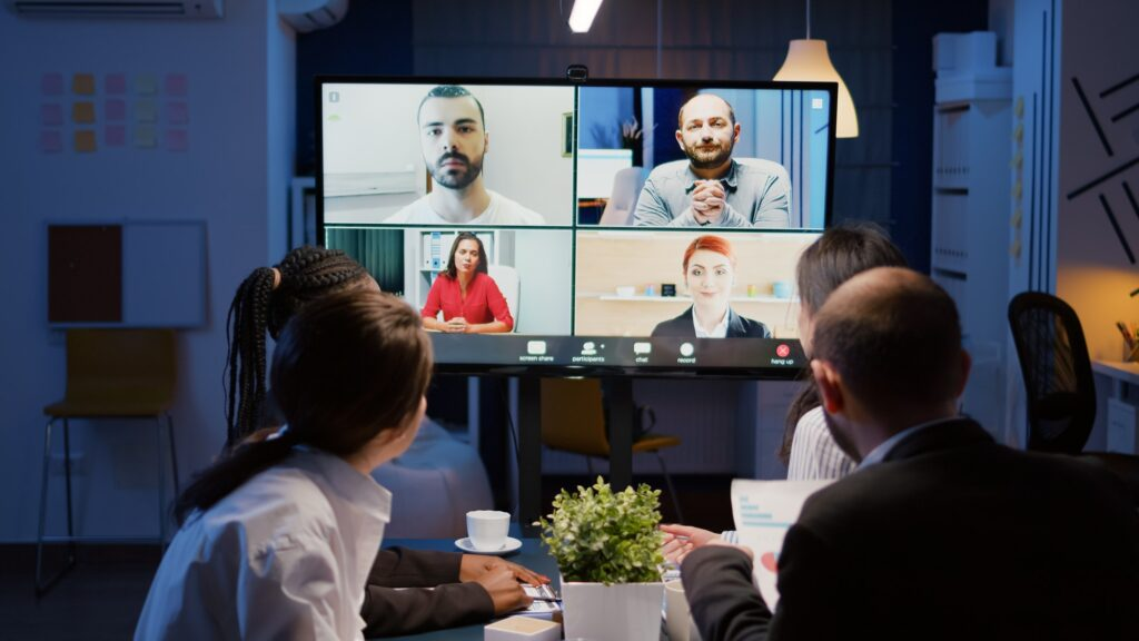 Multi ethnic businesspeople discussing company statistics with remote coworkers